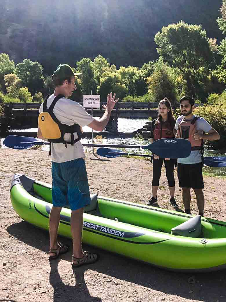 Two adults listening to an instructor explain river rafting and kayaking safety during a training class on the Provo River Utah.