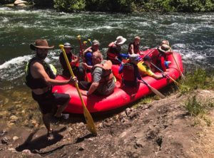 River guide and boy scouts on a raft during a river rafting, kayaking and tubing trip on the Provo River in Utah.