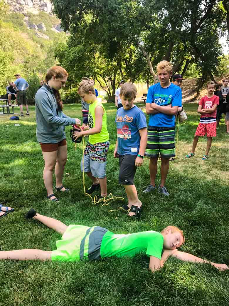 A rafting and kayaking instructor shows Boy Scouts how to throw a throw rope to a person who needs assistance.