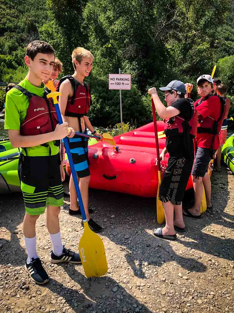 Boy Scouts standing by rafts with paddles in their hands as they wait for their river rafting and kayaking trip on the Provo River in Utah to begin.