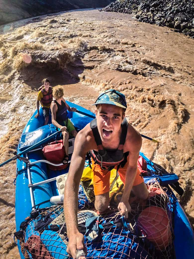 Three guys in a selfie photo who are rafting through a whitewater rapid on the Colorado River in the Grand Canyon.