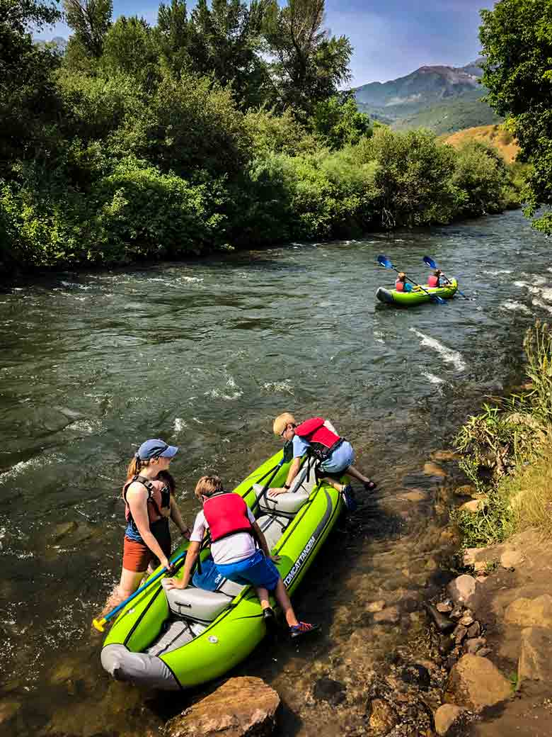 A guide helps boys into a kayak during a Provo River kayak trip in Utah.