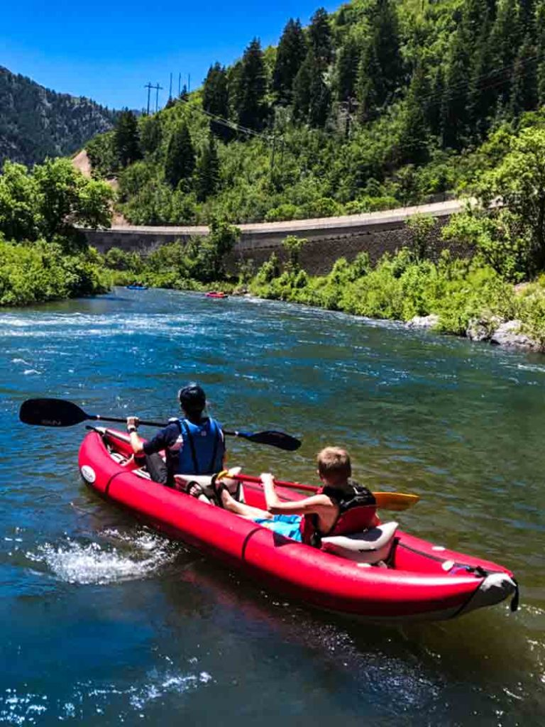 Two people kayaking on the Provo River near Orem and Park City Utah.