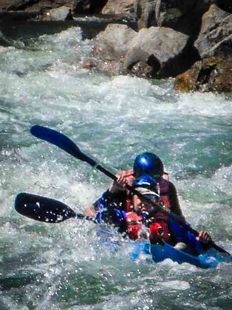 Two people whitewater kayaking on the Kern River in Kernville California.