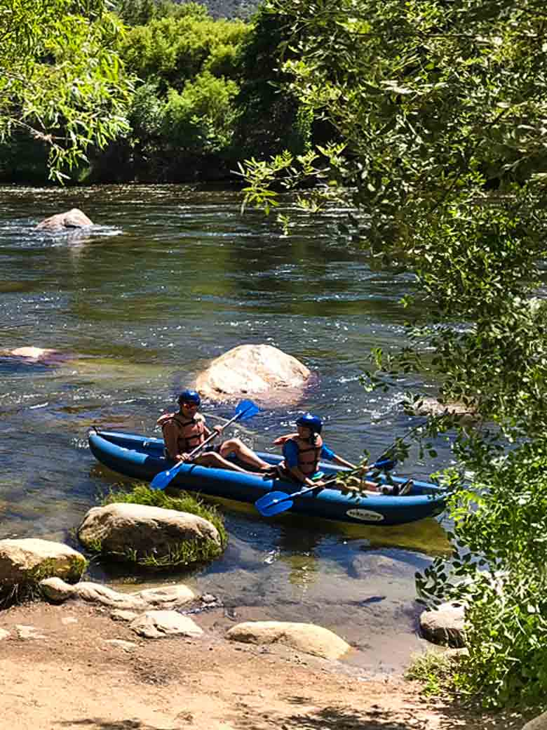 Two people about to start a whitewater kayak river trip on the Kern River in the Sequoia National Forest in California.