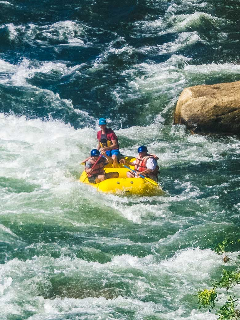 Men whitewater rafting in a yellow raft on the Kern River in Kernville California.