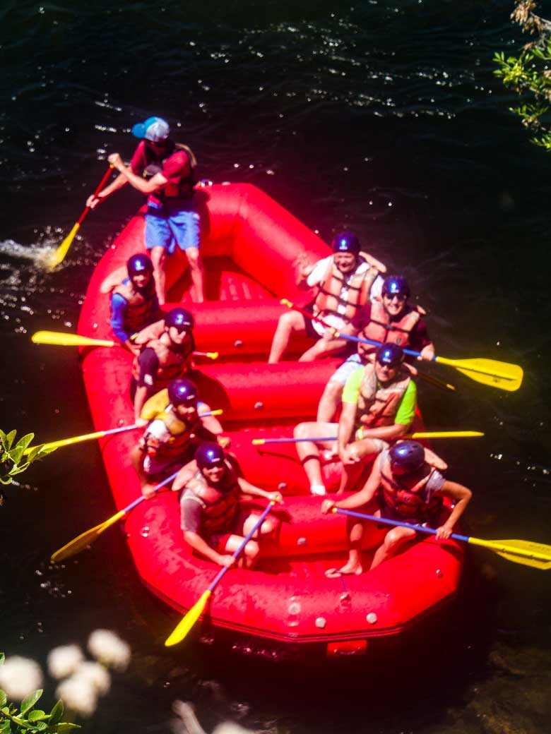 Men rafting in a red raft during a whitewater rafting trip on the Kern River near Kernville California.