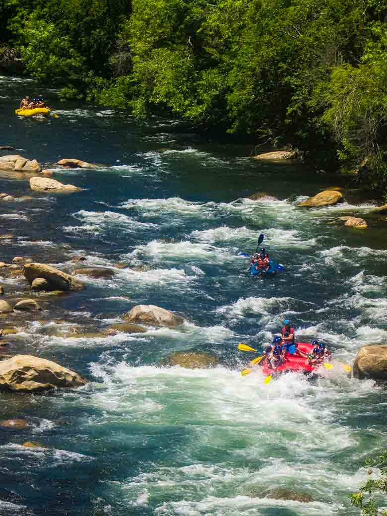Men whitewater rafting and kayaking through Ewings rapid on the Kern River in Kernville California.