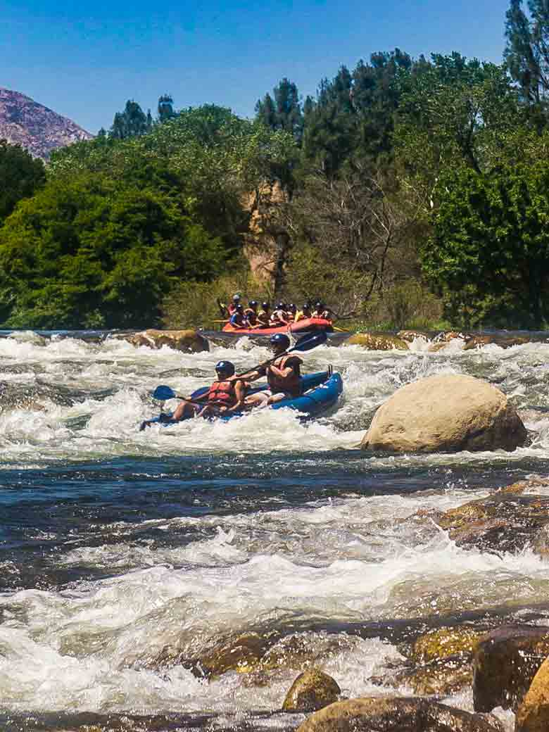 Two groups rafting and kayaking through Big Daddy rapid on the Kern River near Kernville California.
