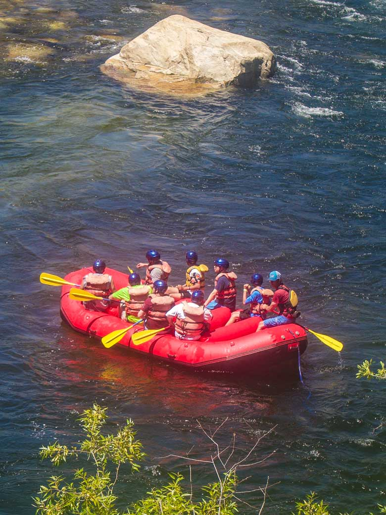 Men whitewater rafting in a red raft on the Kern River in Kernville California.