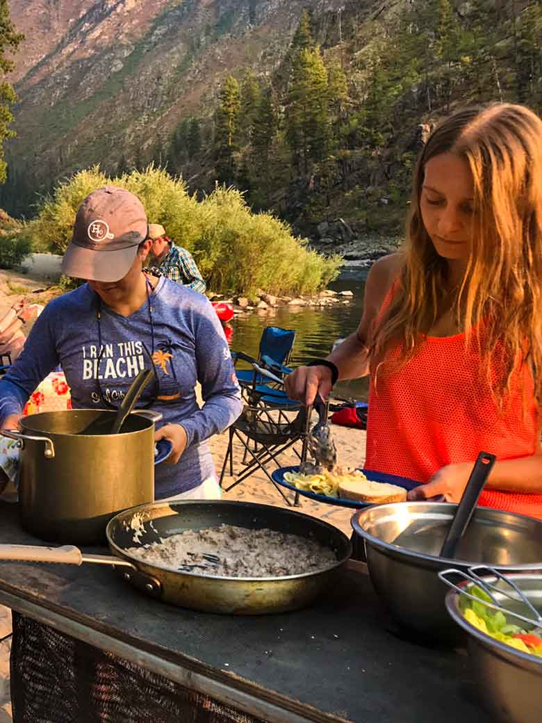 Two girls serving dinner during a Main Salmon River whitewater rafting vacation in Idaho.