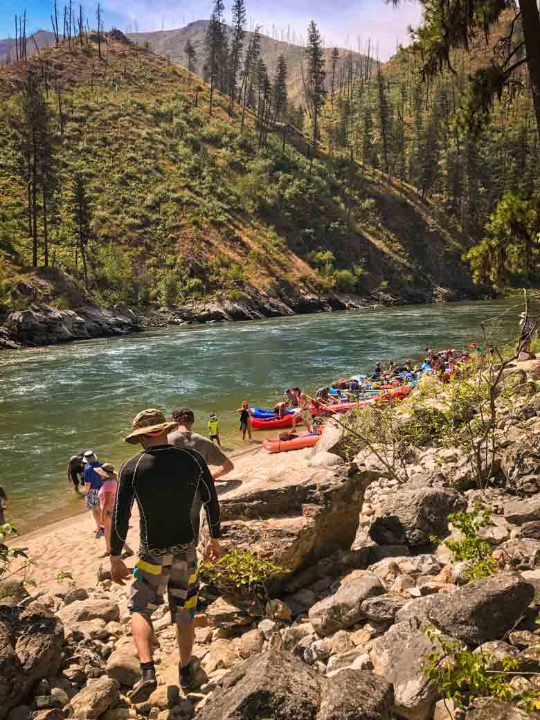 A group hiking to rafts and kayaks along the river during a Main Salmon River whitewater rafting vacation in Idaho.