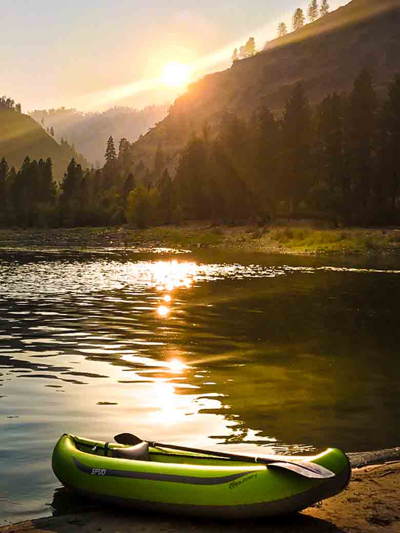 A kayak in a beach at sunset during a Main Salmon River whitewater rafting vacation in Idaho.