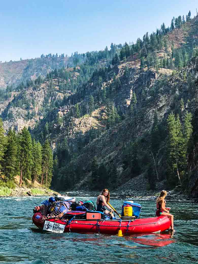Two girls rafting during a Main Salmon River whitewater rafting vacation in Idaho.