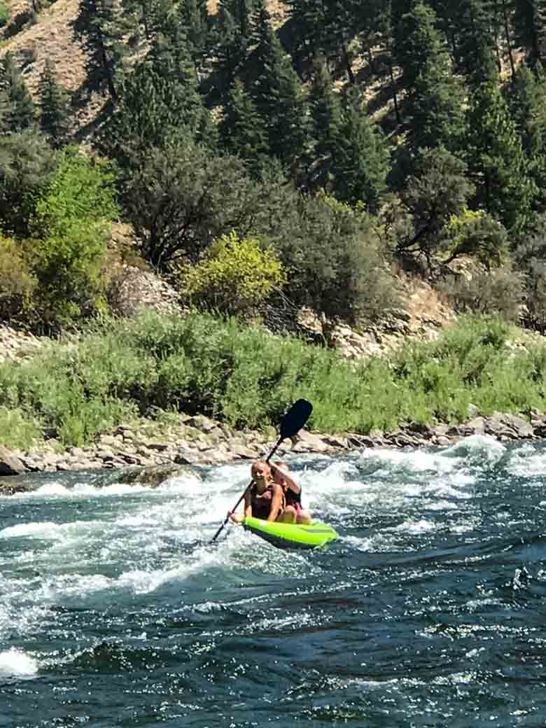 Two girls kayaking during a Main Salmon River whitewater rafting vacation in Idaho.