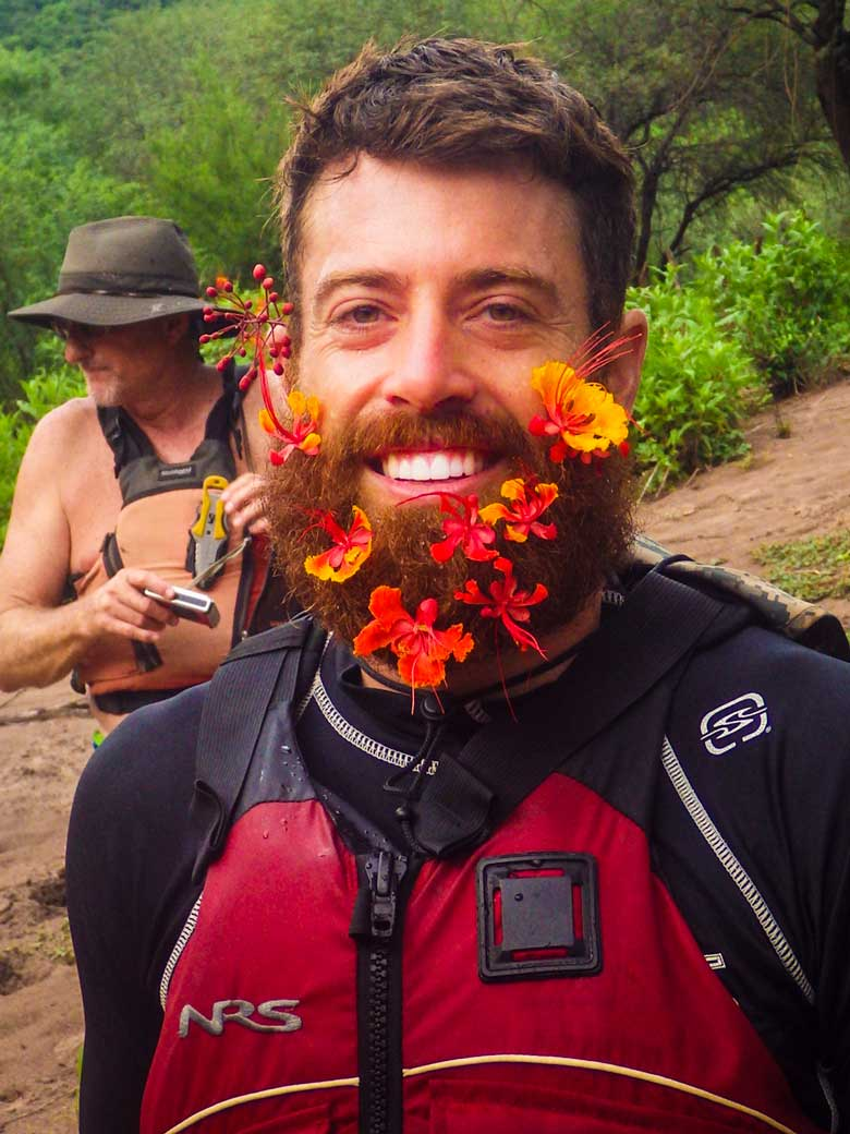 A man wearing wild flowers in hs beard during a whitewater river rafting trip in Mexico.