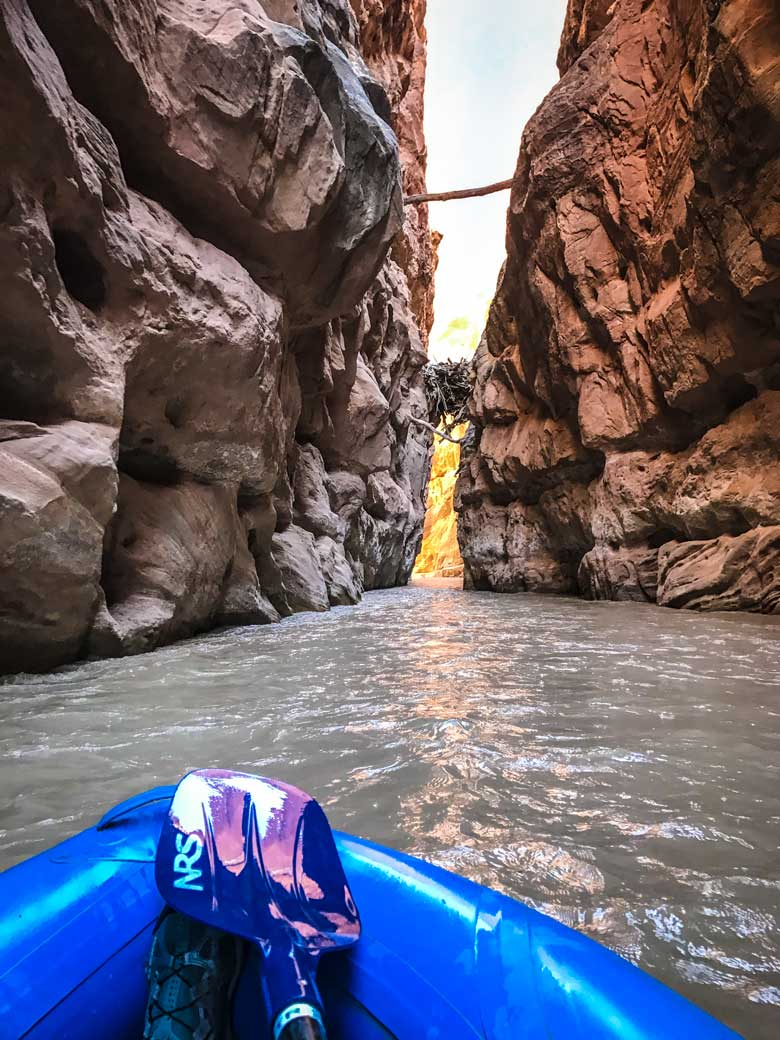 A narrow slot canyon and a blue kayak on a river rafting trip near Moab and Capitol Reef National Park in Utah.