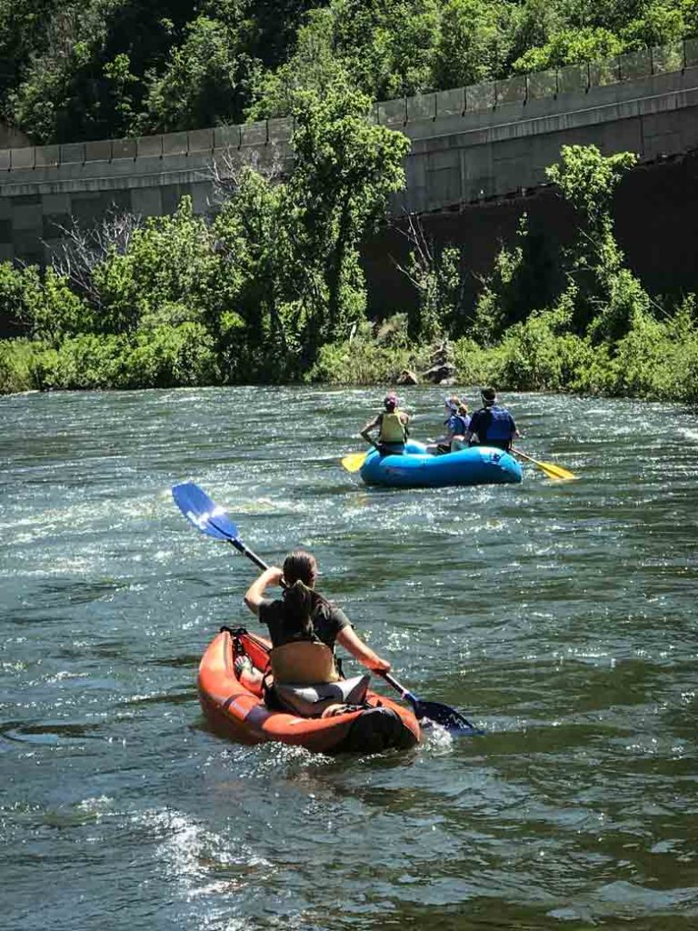 A person kayaking in a red kayak and a group rafting in a blue raft during a river trip on the Provo River.