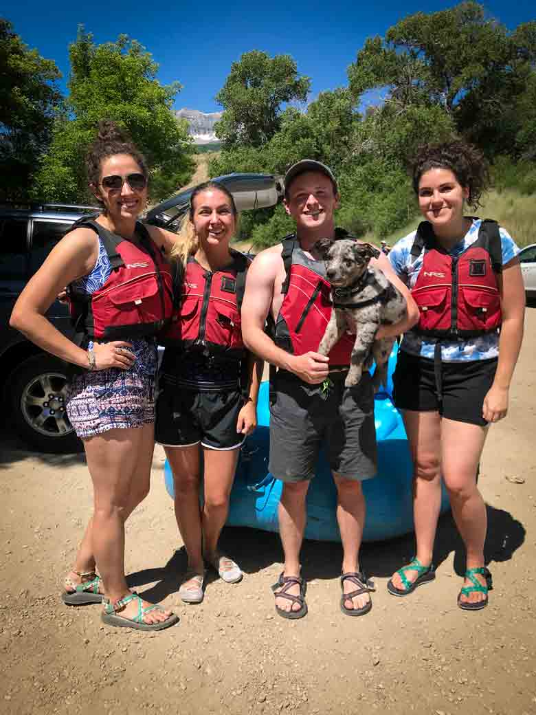 A group of people posing with a dog after a rafting and kayaking trip on the Provo River near Orem and Park City Utah.
