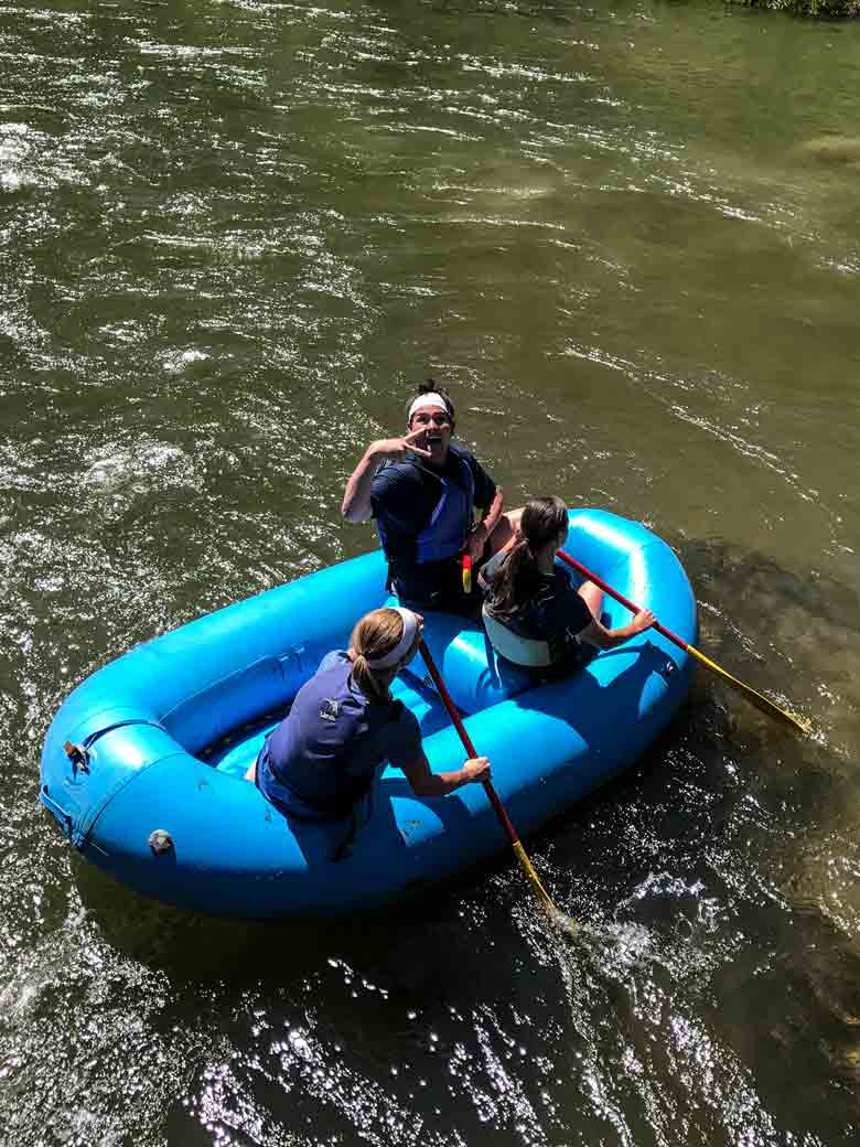 A group of three rafting in a blue raft on the Provo River near Provo and Park City Utah.