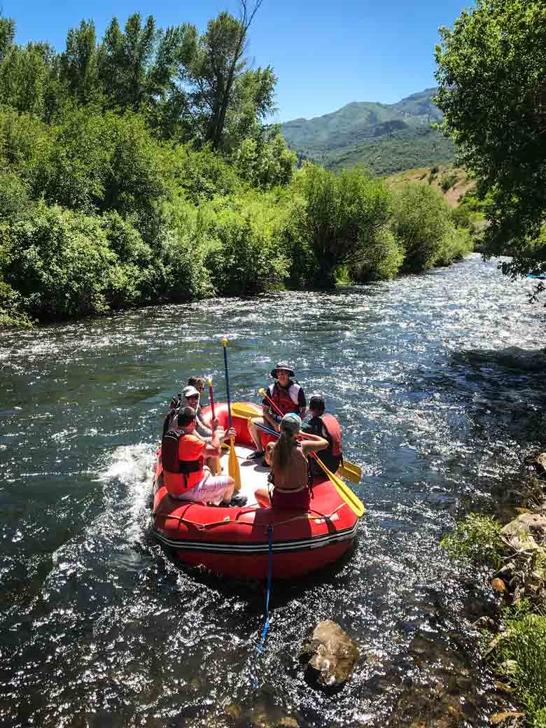 A group of people rafting in a red raft on the Provo River near Orem and Park City Utah.