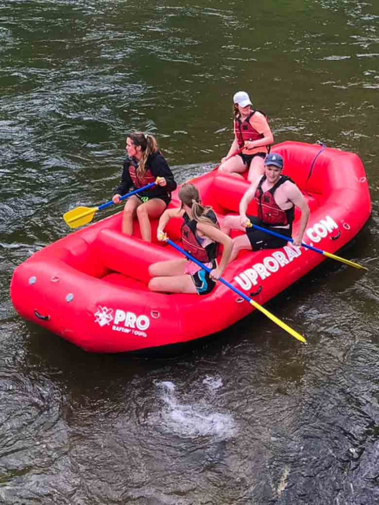 A group of three rafting in a red raft on the Provo River near Provo and Park City Utah.