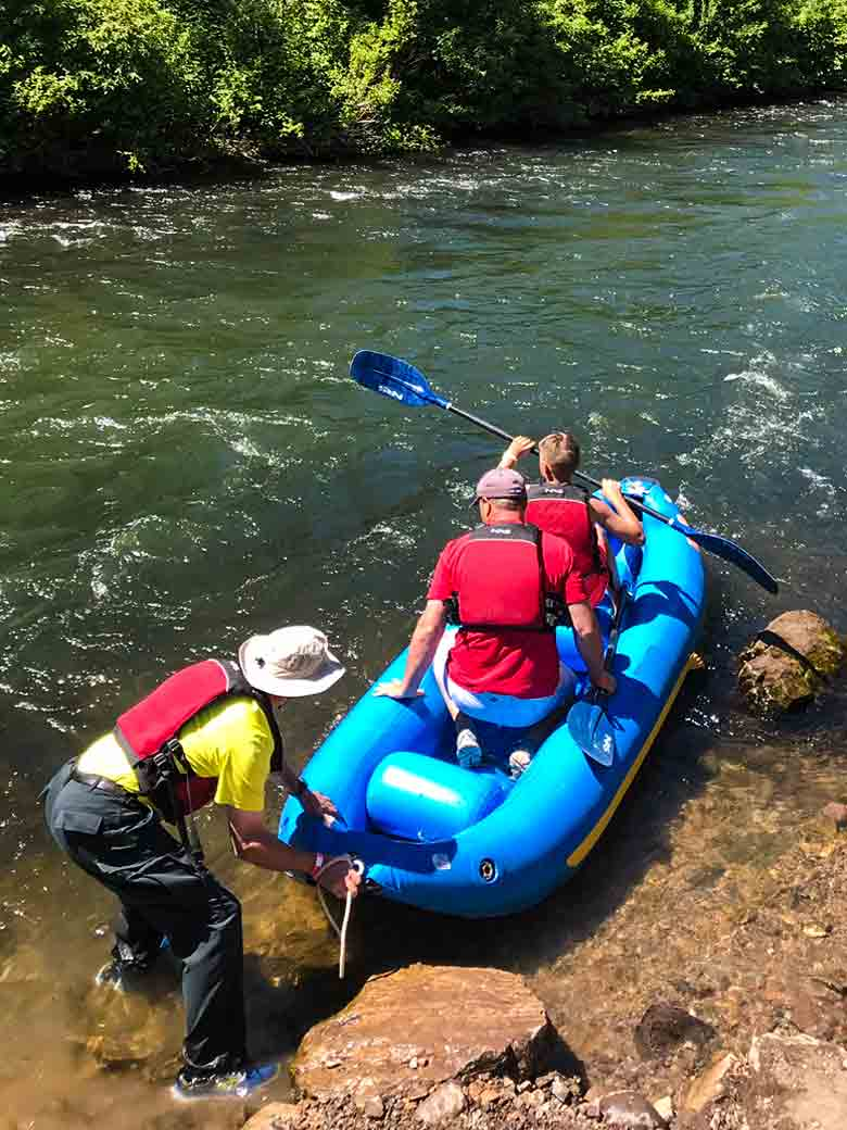 A person helping two people push their kayak into the water during a Provo River kayak trip near Provo and Park City Utah.