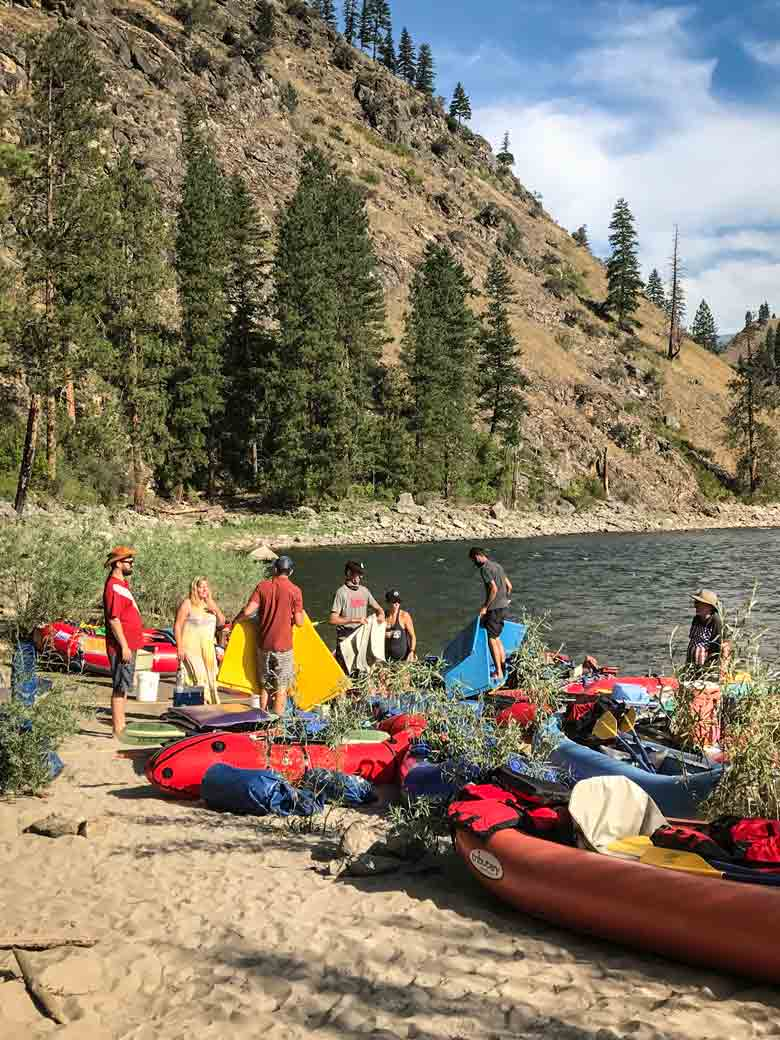 People arrange their rafts, kayaks and river camping equipment during a whitewater river rafting trip in Wyoming.