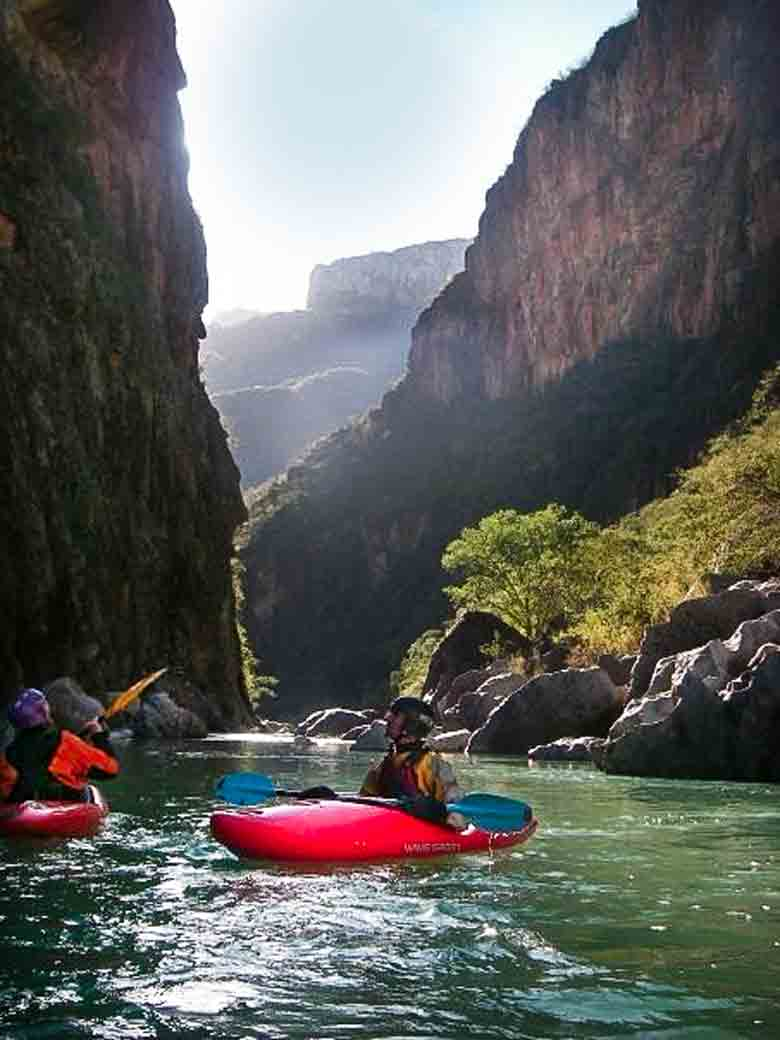 Two men kayaking in Copper Canyon during a whitewater river rafting trip in Mexico.