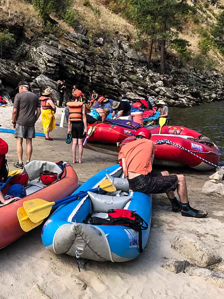 People preparing rafts and kayaks for a whitewater river rafting trip on a Idaho river.