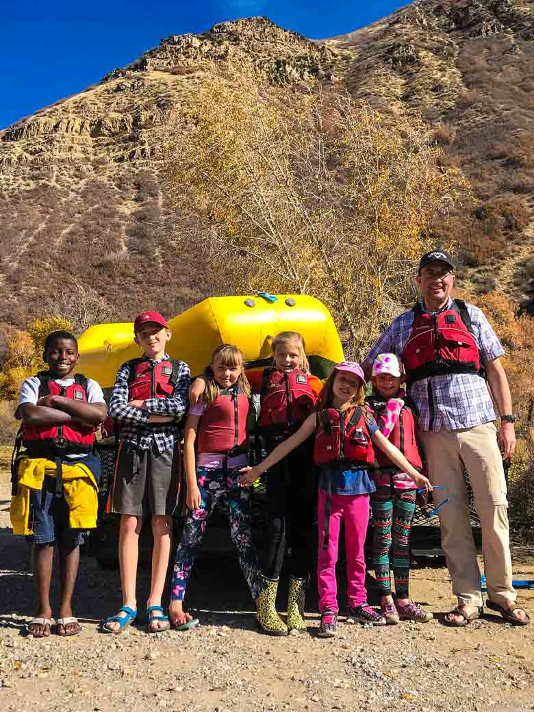 A man with six children standing in front of a yellow raft before they take a youth river skills training class on the Provo River in Utah.