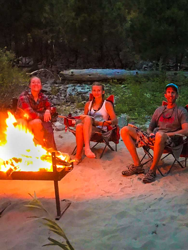Three people enjoying a campfire during a whitewater rafting trip on the Main Salmon River in Idaho.