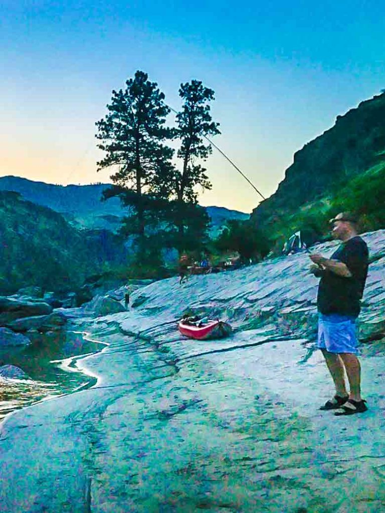 A man fishing at camp during a Main Salmon River whitewater rafting trip in Idaho.